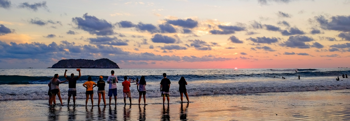 Group of students on a beach at sunset